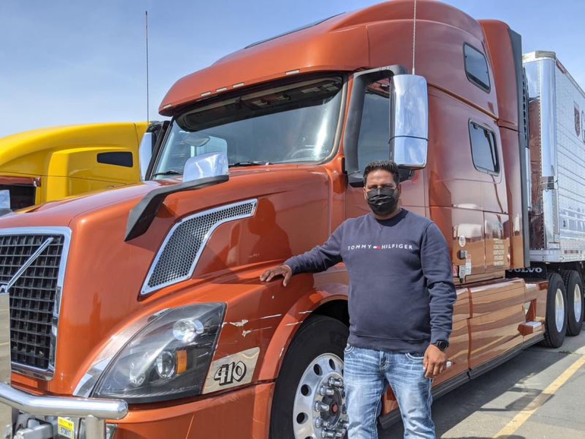 a man in jeans, a long sleeve shirt, and face masks stands in front of a large orange transportation truck.