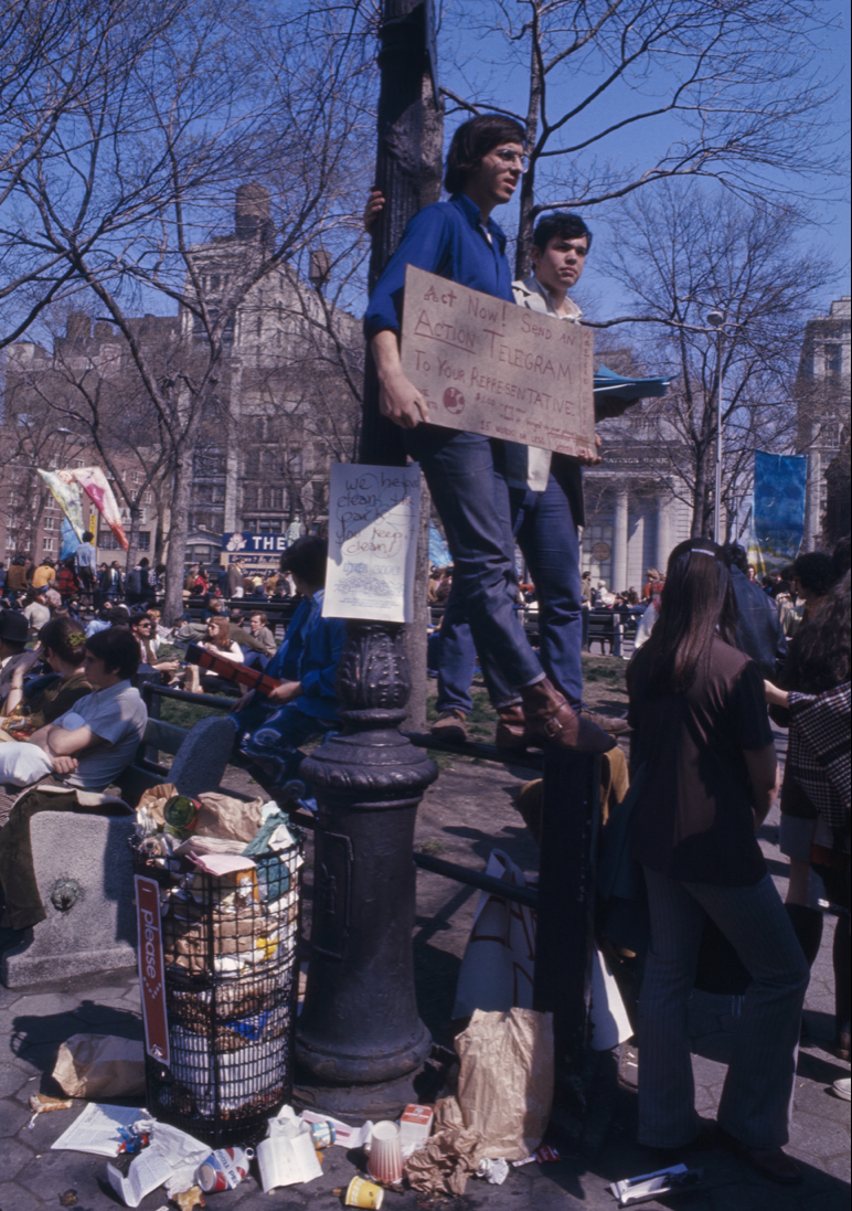 """a crowd of people in new york, with the focus on a man in a blue shirt and glasses holding a cardboard sign that says """"act now."""" he and another man are standing up against a tree. next to them is a trash can completely overfilled with trash"""