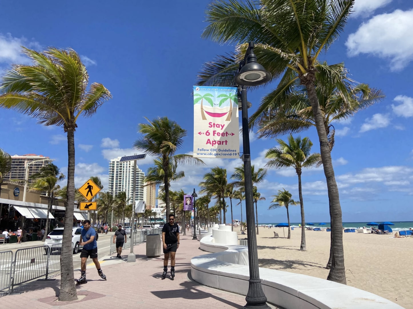 a daytime shot of the fort lauderdale boardwalk with palm trees and people rollerblading. a sign hangs from a lamppost saying 'stay 6 feet apart, follow cdc guidelines'