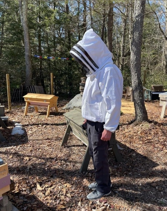 a figure stands in jeans and a white beekeeping top with a hood and veil, against a forest backdrop