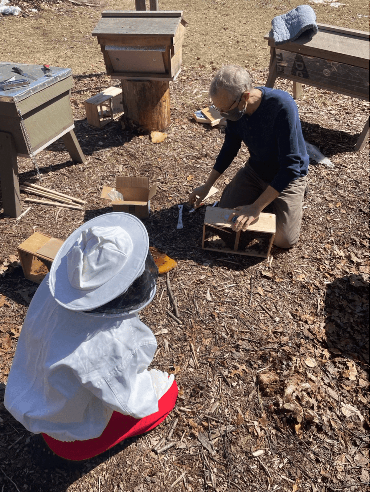 two people - one wearing a beekeeping suit and one in plain clothes - crouch over beekeeping materials in the dirt