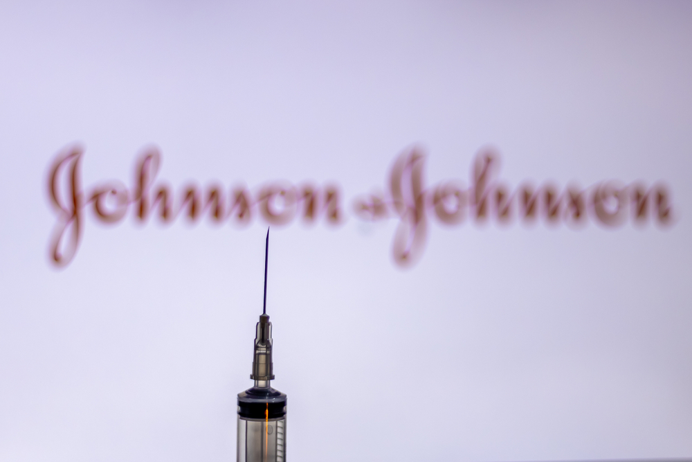a needle in the foreground and the johnson and johnson logo in the background