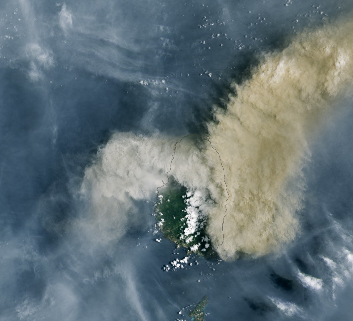 a satellite image of st vincent island, mostly shrouded by the plume of a volcano, drifting off to the right