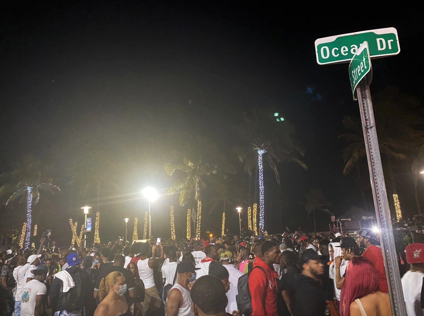 a large throng of people at night, tightly packed without masks. a street sign is in the foreground with palm trees decorated with string lights in the background