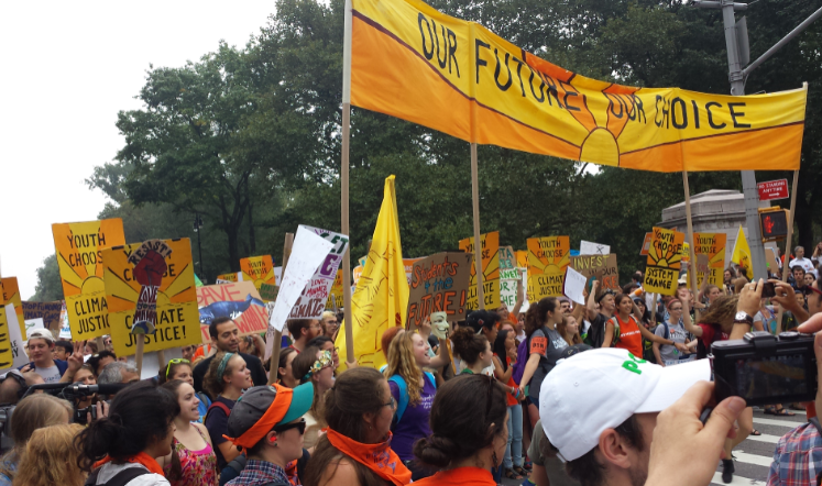 """a large crowd of young people marching with yellow signs that read """"our future, our choice"""""""