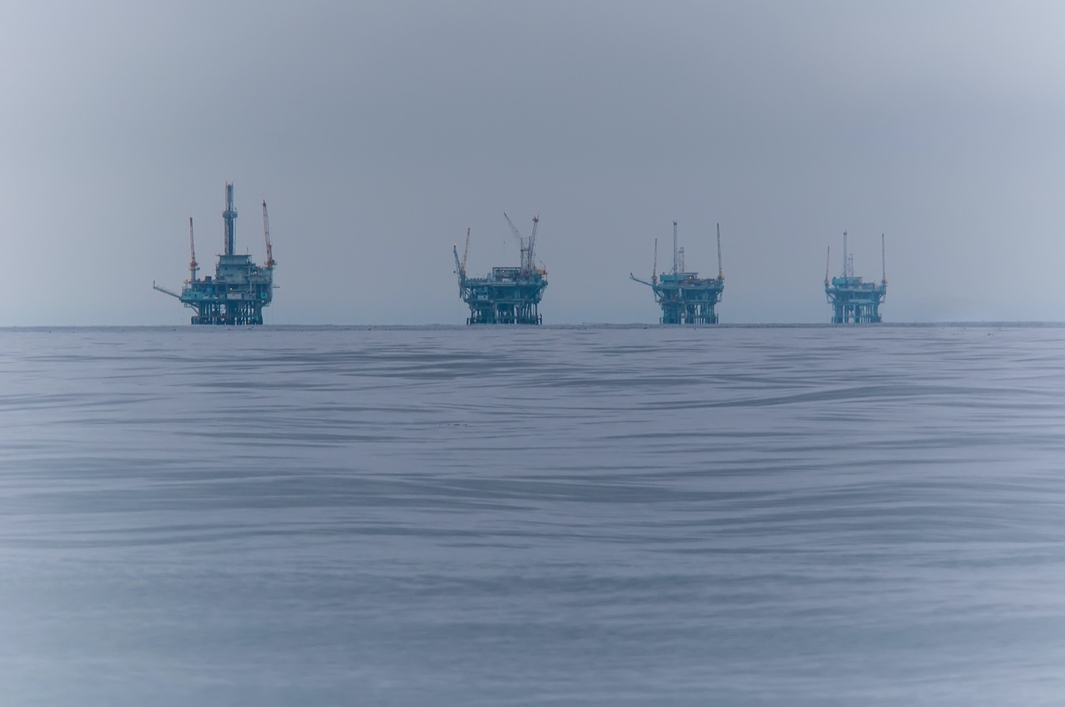 four oil rig platforms seen out in the misty distance on the horizon of the ocean