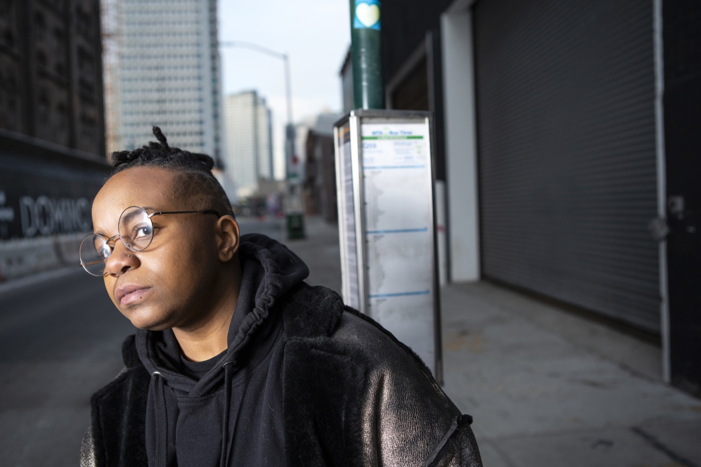 A transmasculine person waiting for the bus in a city close up