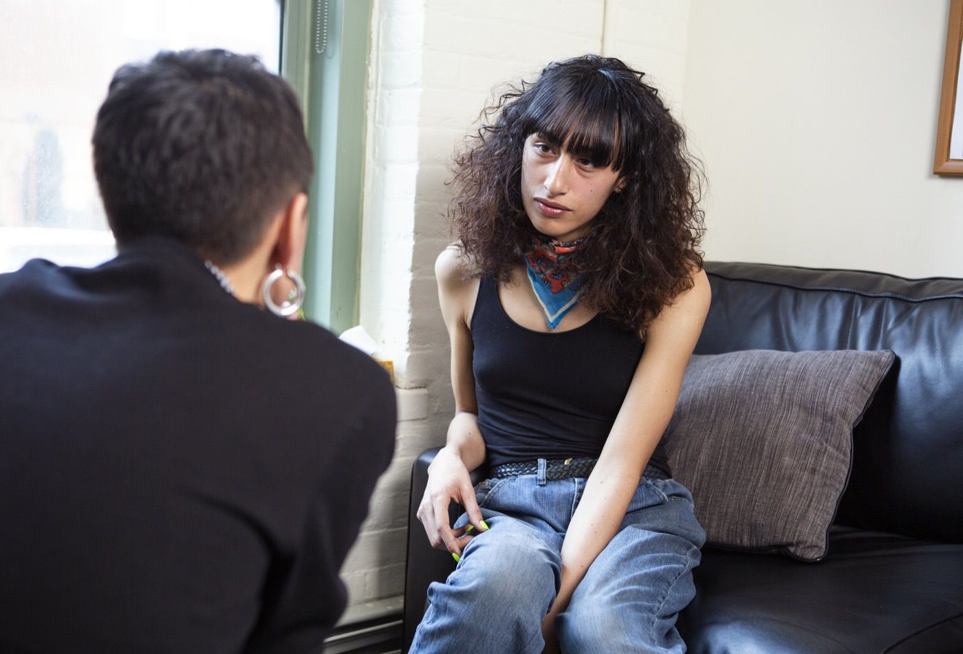 A transgender woman sitting on a therapist's couch and listening