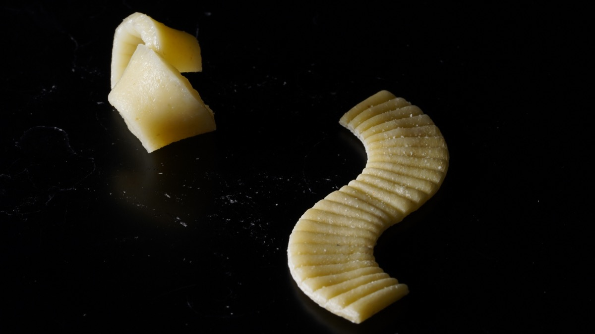 two pieces of pasta side by side. on the right is the pasta flat in a curved s-shape, on the left is that pasta after boiling in a curled up shape