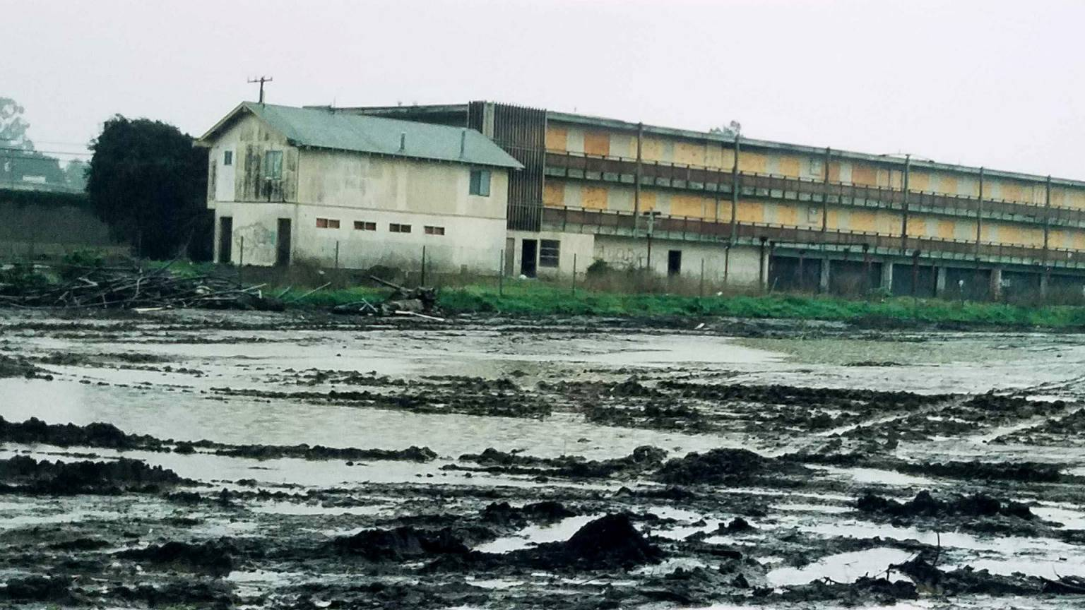 industry buildings and sheds flooded by murky muddy water