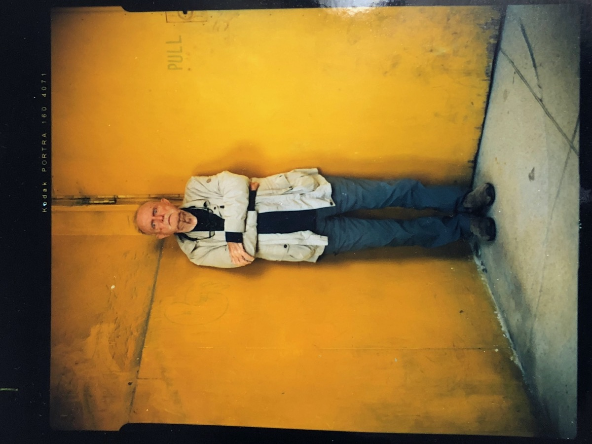 an older man in a denim shirt standing against a yellow background