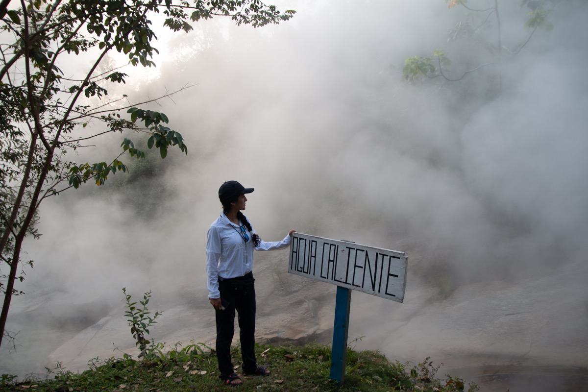 """a woman scientist wearing gloves looks at a steaming river next to a sign in Spanish labeled """"AGUA CALIENTE"""" (hot water)"""