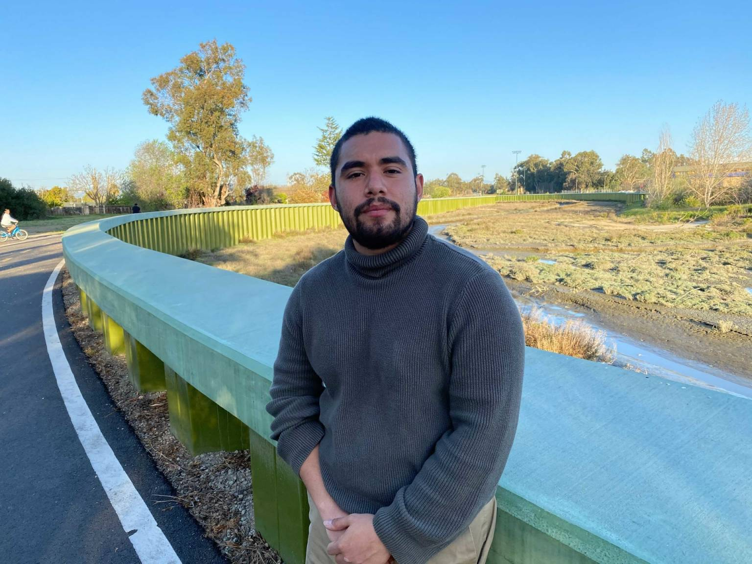 a man with a beard wearing a gray sweater leaning against a railing along the road