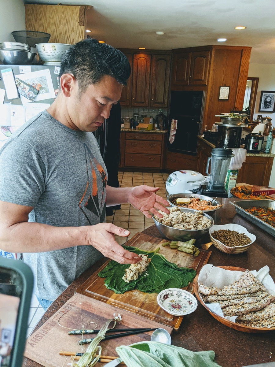 an asian man making sushi with cicadas in a kitchen