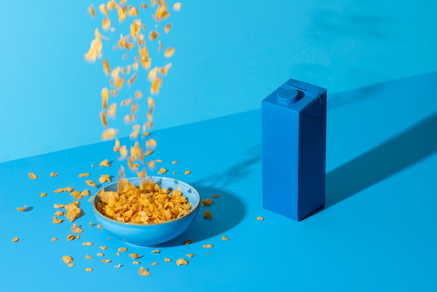 a waterfall of corn flakes falling into a blue bowl on a blue table with a blue carton of milk nearby