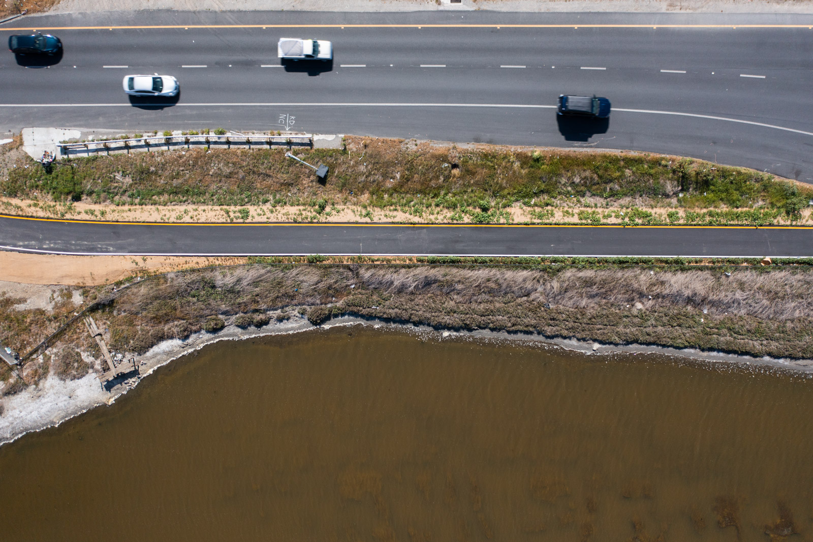 an aerial view of a bridge with a road with cars driving across water