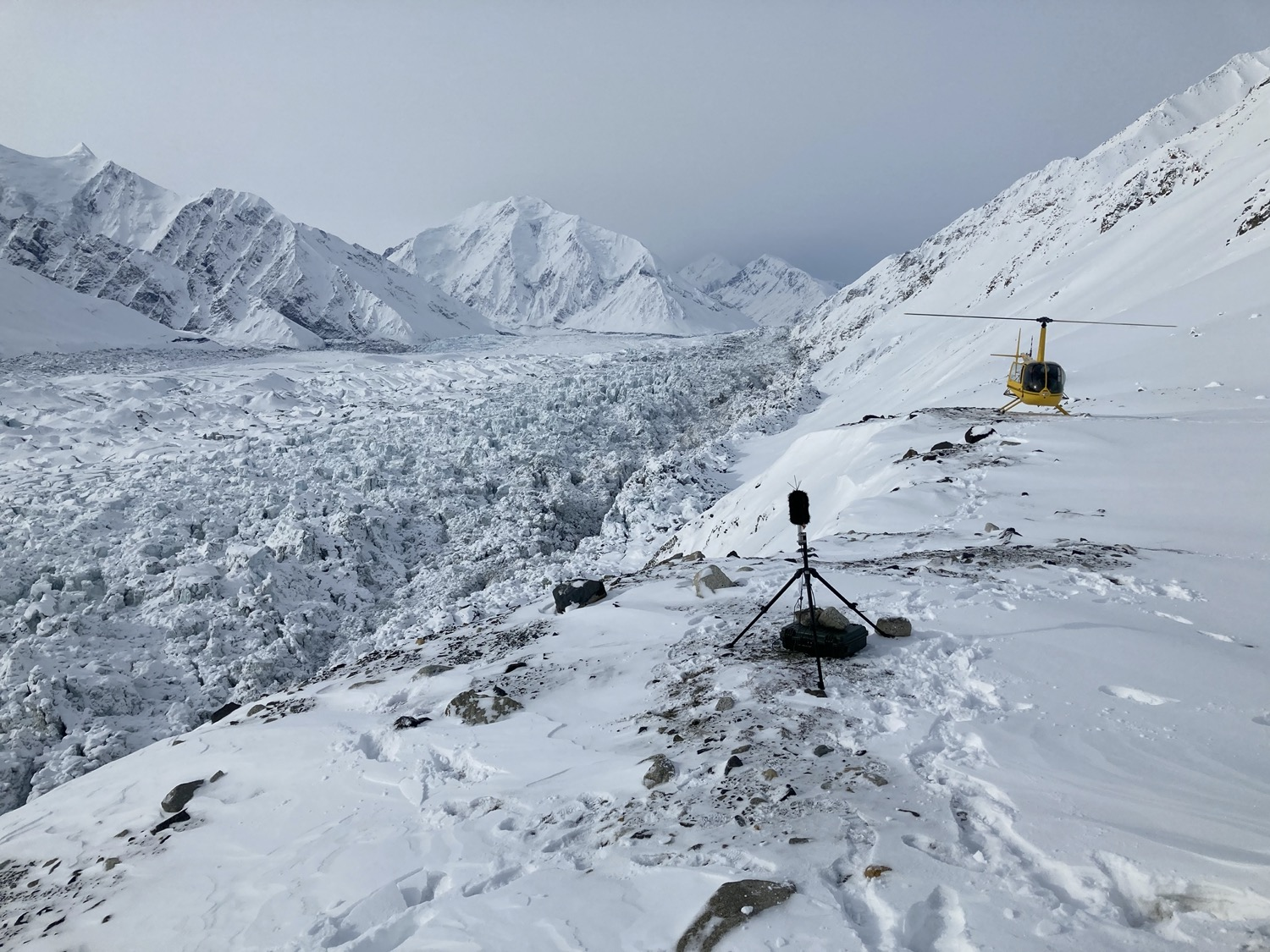 a snowy mountainous landscape, with a microphone on a tripod and a yellow helicopter in the background