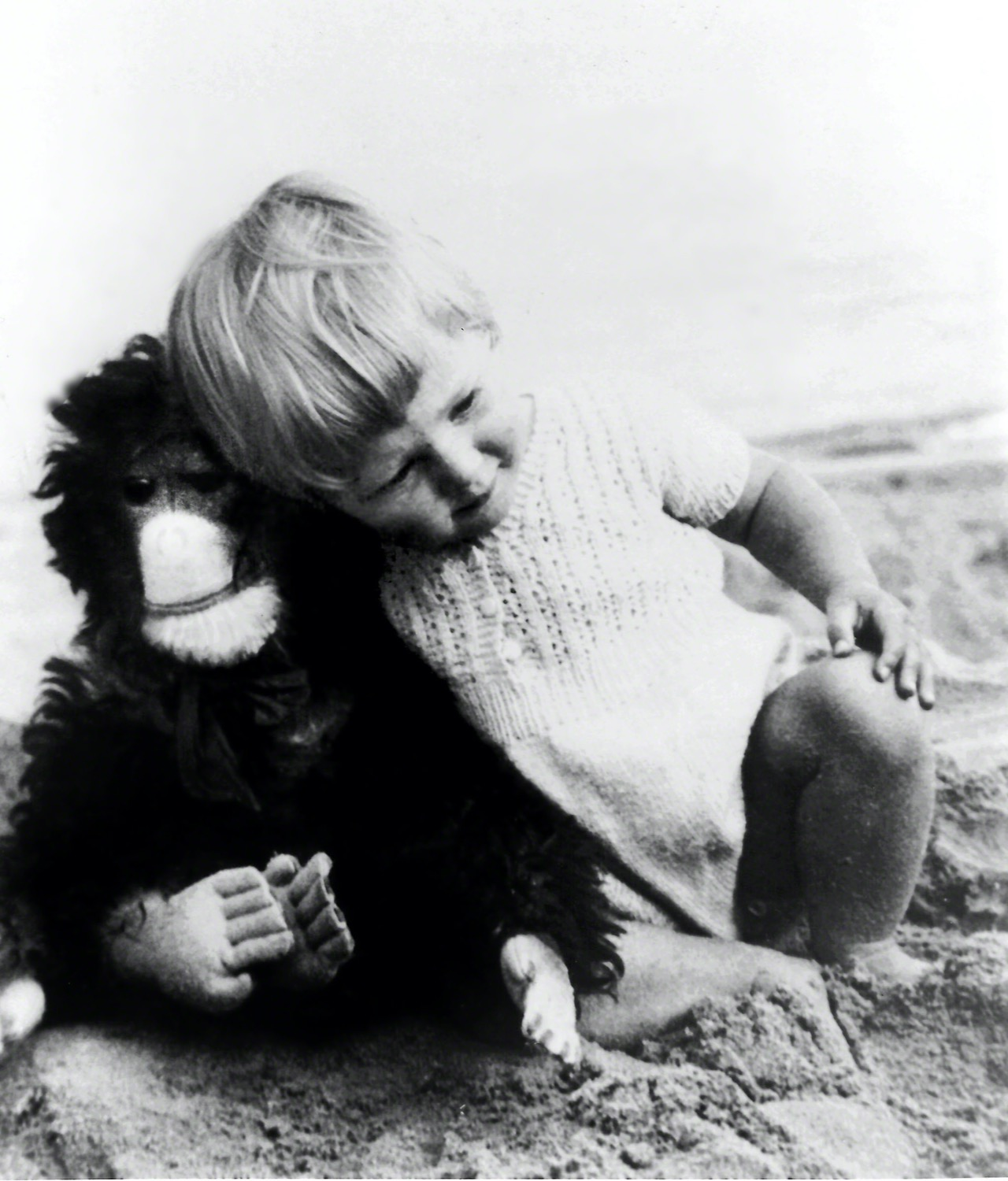 black and white image of a young girl with a monkey doll