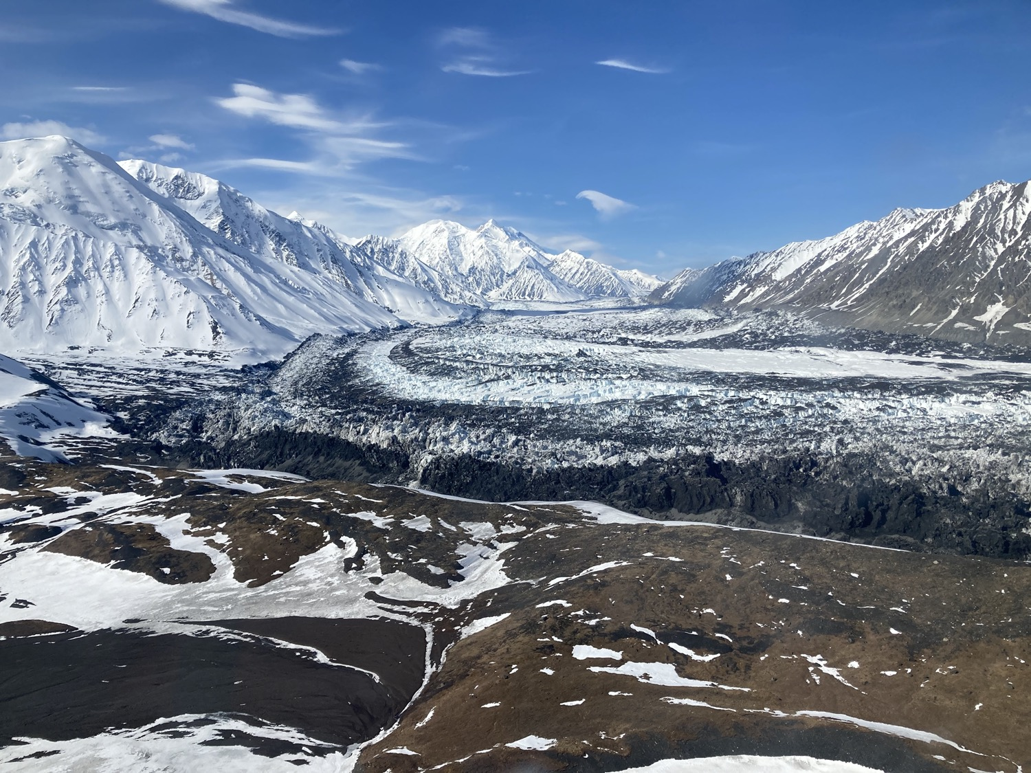 a mountainous landscape, half covered in snow, with a sweeping flat glacial body in the center at the foot of the mountains