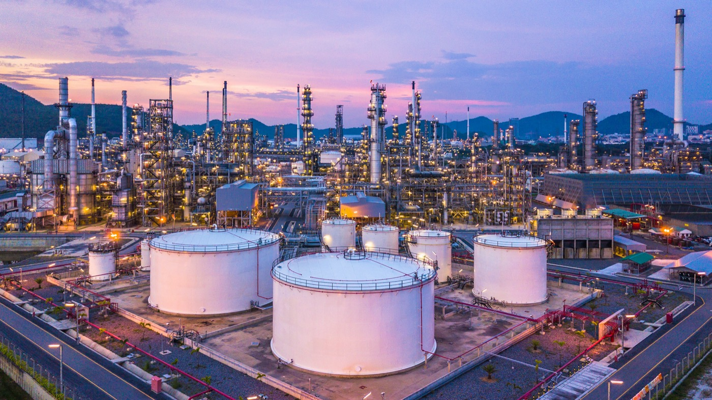 aerial view of a sprawling oil refinery with many round large tanks and myriad pipes