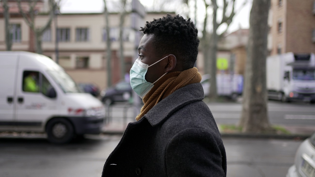 a black person wearing a mask on the street with cars and buildings behind them