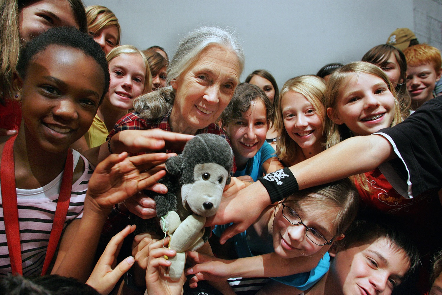an older woman holds a stuffed monkey and is surrounded by smiling children