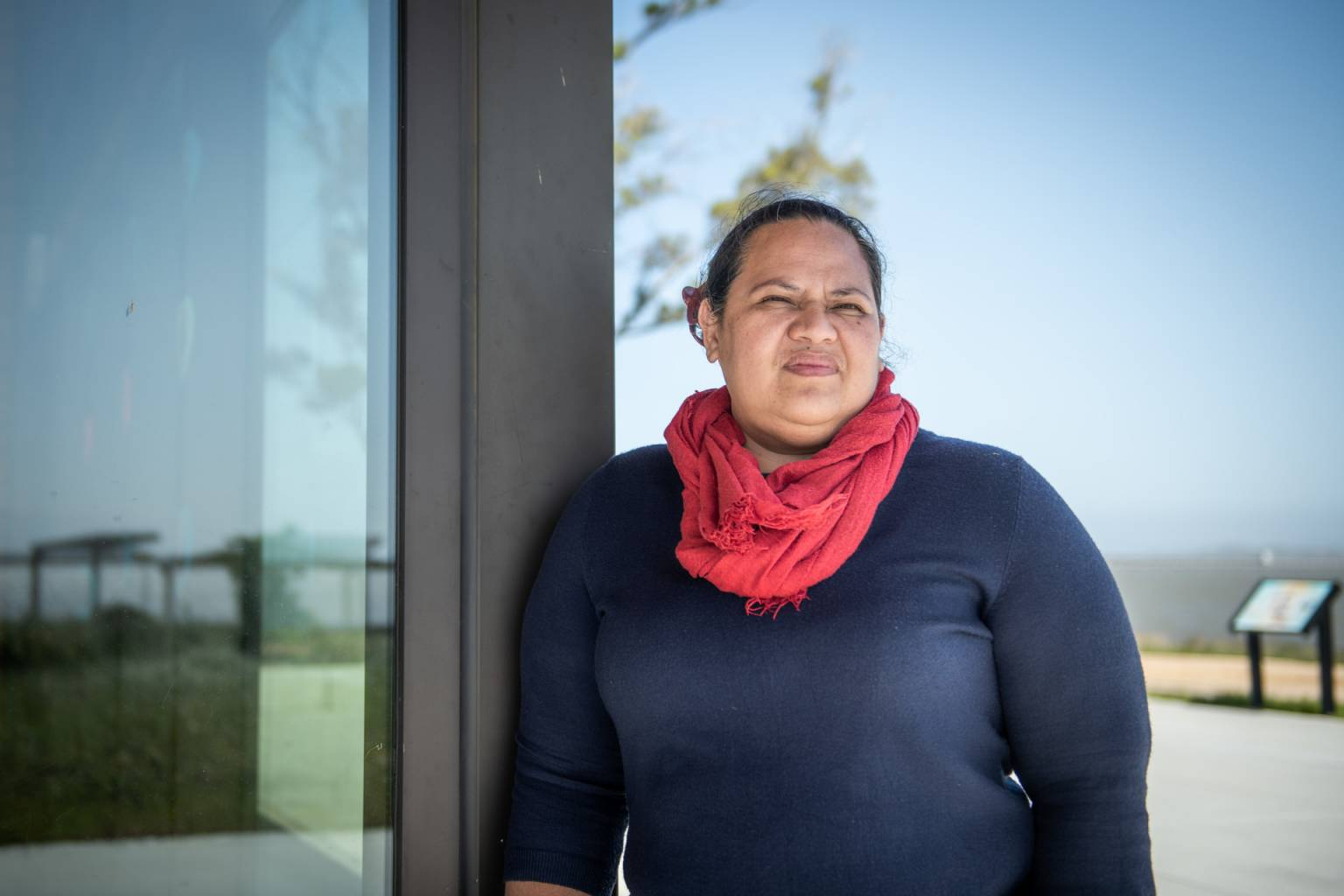 a samoan woman in a red scarf and navy shirt leaning against a glass door