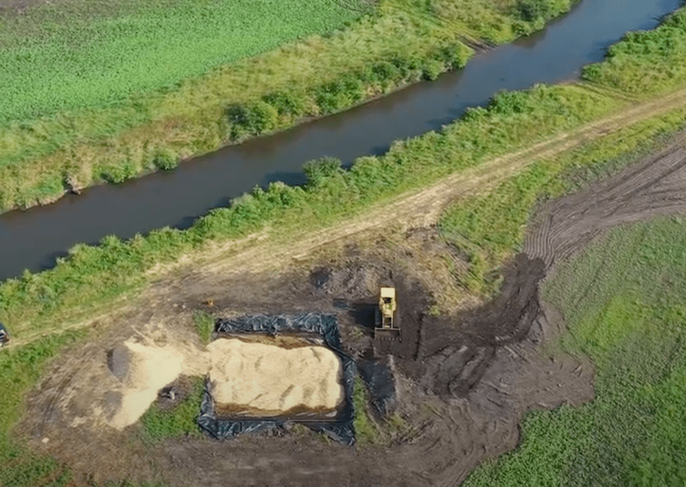 an aerial view of a large pile of woodchips and a trench of them with a tractor nearby. close to the trench is a small river