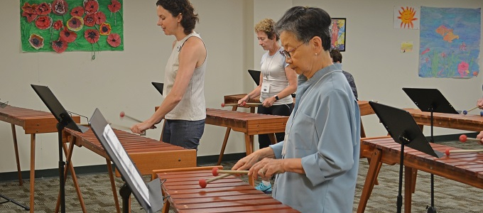 a group of people playing xylophones in a class, with the main focus on an older asian woman with short hair
