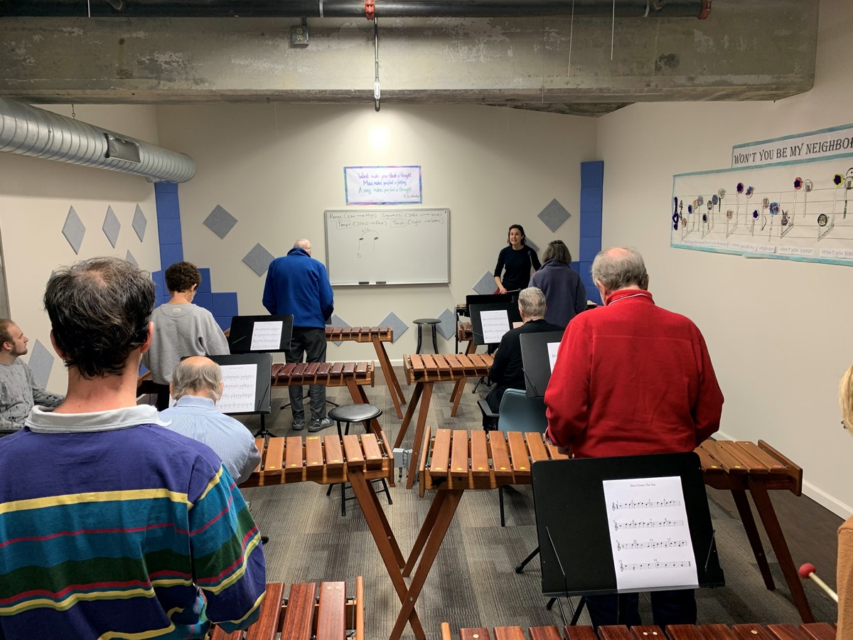 a class of elderly people playing xylophones with an instructor at the front