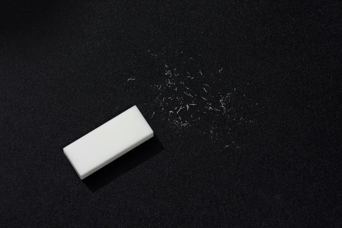 white eraser with scraps against a black background