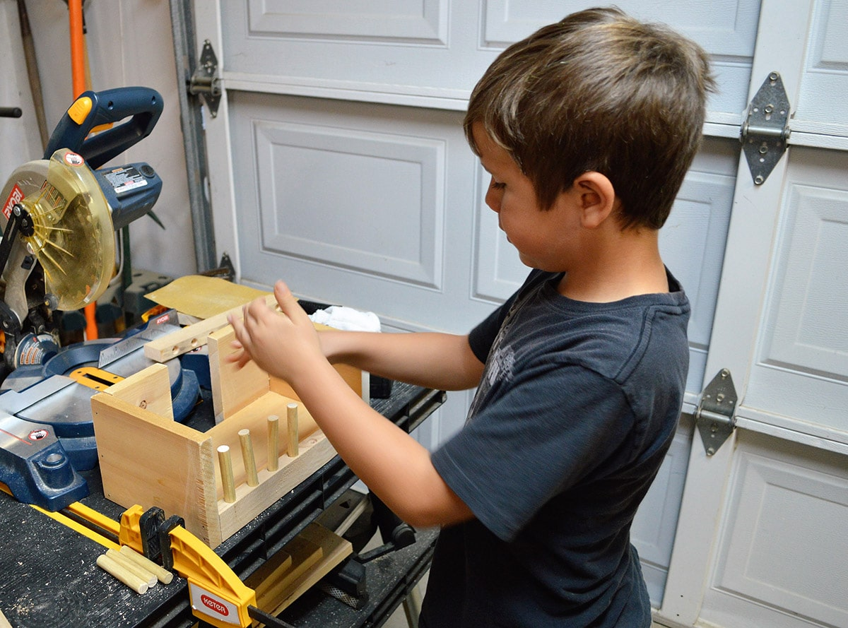 Young boy working on building a puzzle box out of wood.