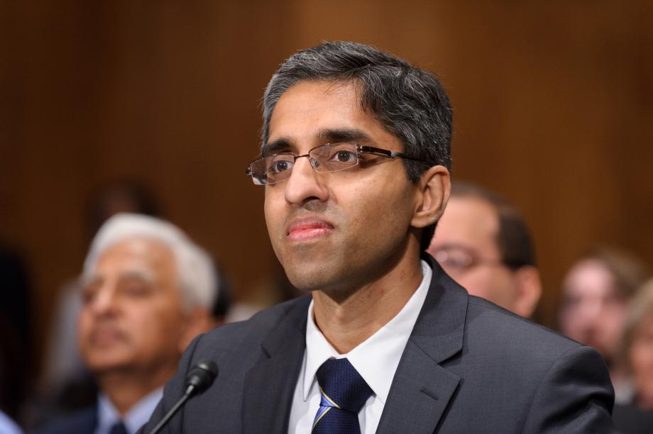 an indian man wearing glasses and a suit tie with a small microphone in front of him, with a small crowd of people behind him