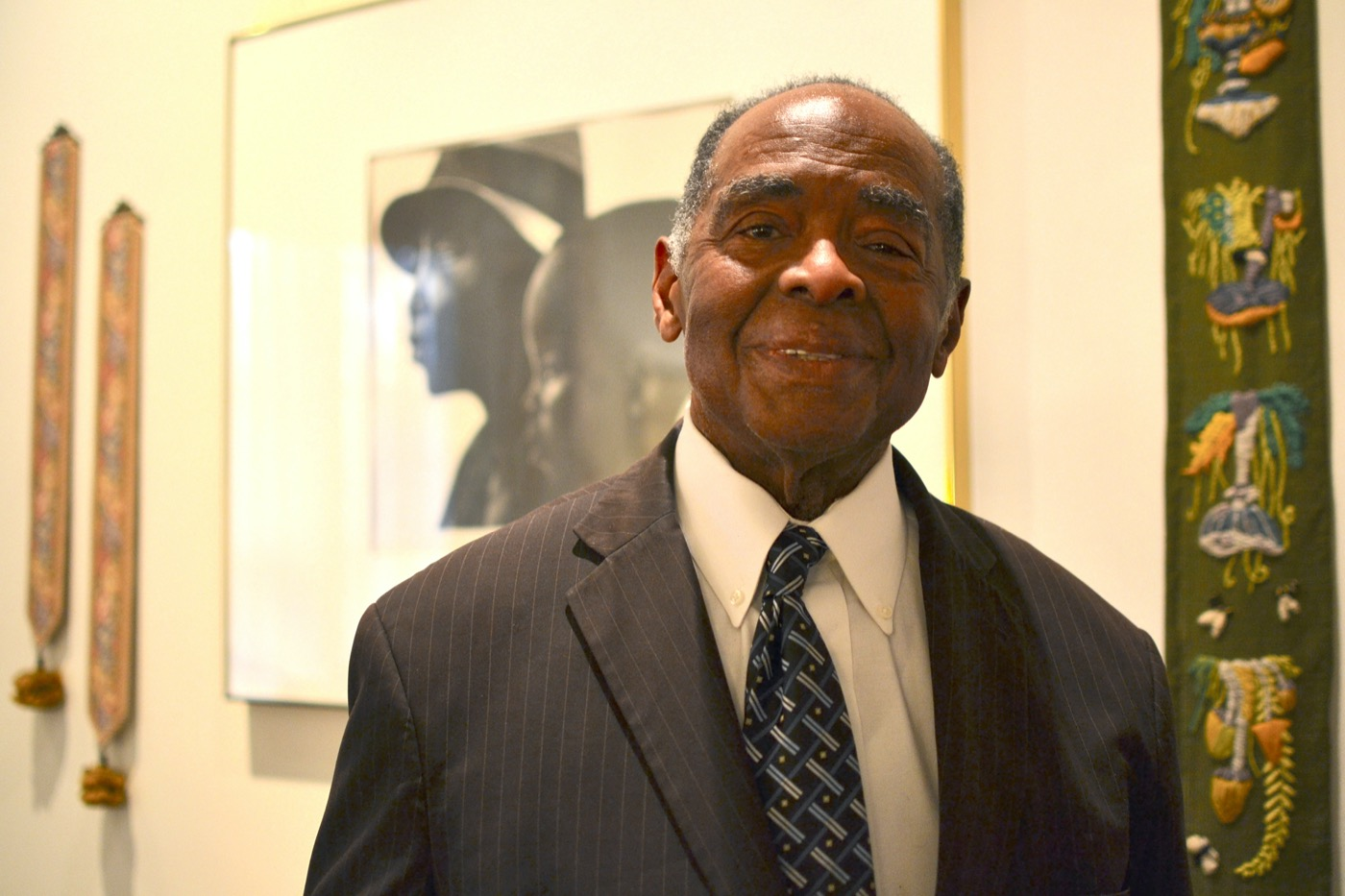 a black man in a suit with a large framed photograph behind him smiles at the camera