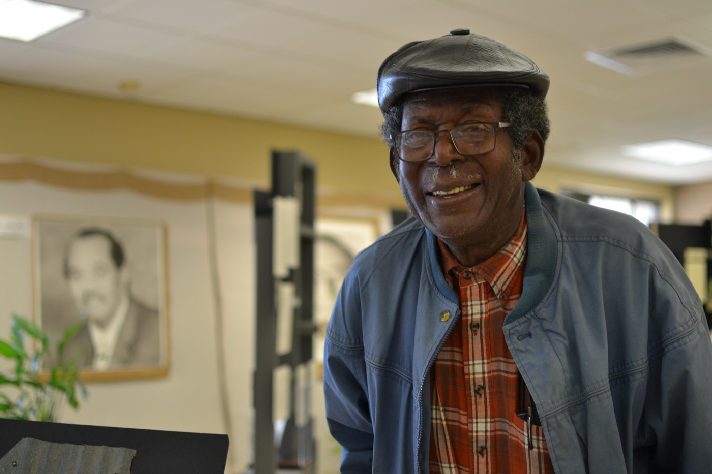 an older black man wearing a jacket and cap smiles at the camera