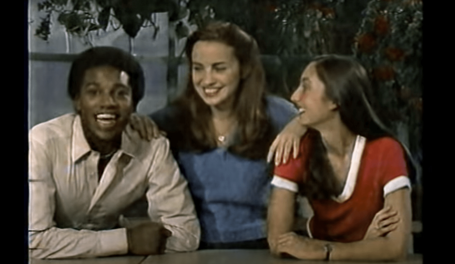 an old grainy color tv image of three people smiling and looking at the camera (a Black man, and two white women). the white woman in the center is leaning on the other two people's shoulders