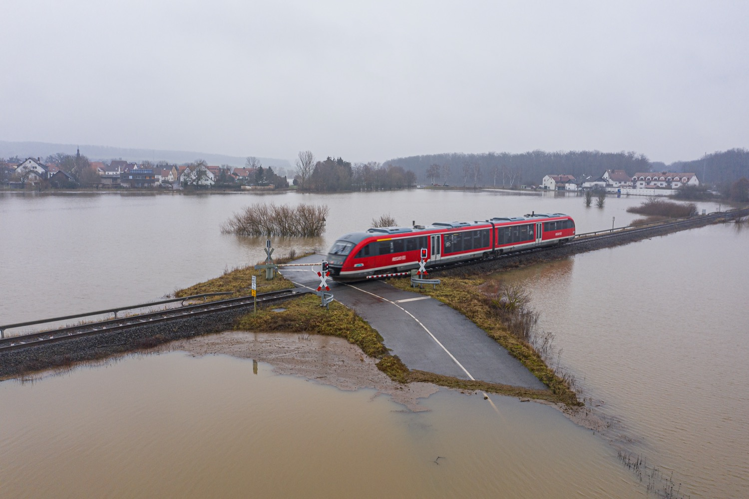 a small train passes over a flooded landscape, with a road partially submerged