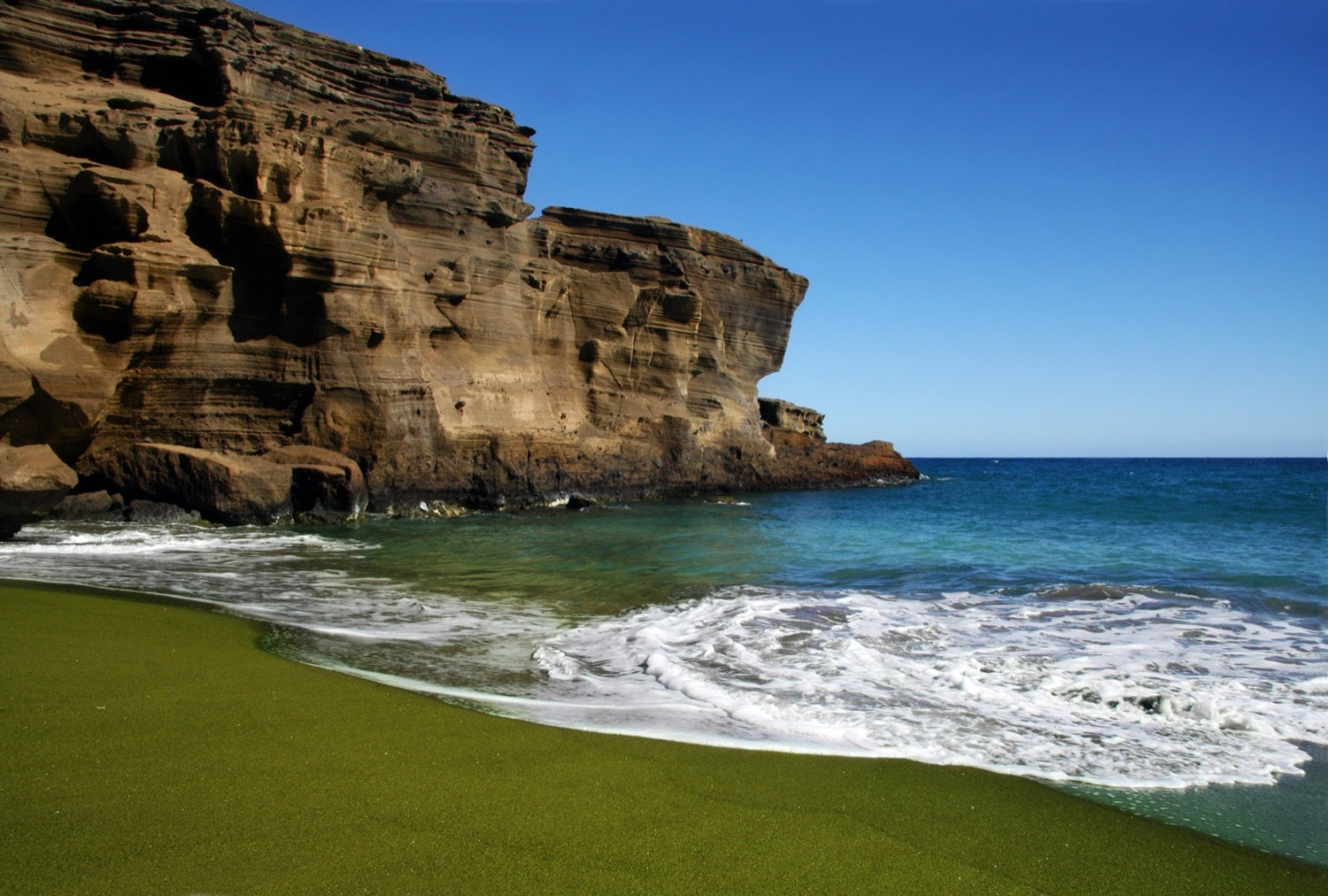 a beach with green sand that looks the shade of moss. in the horizon are weathered cliffs