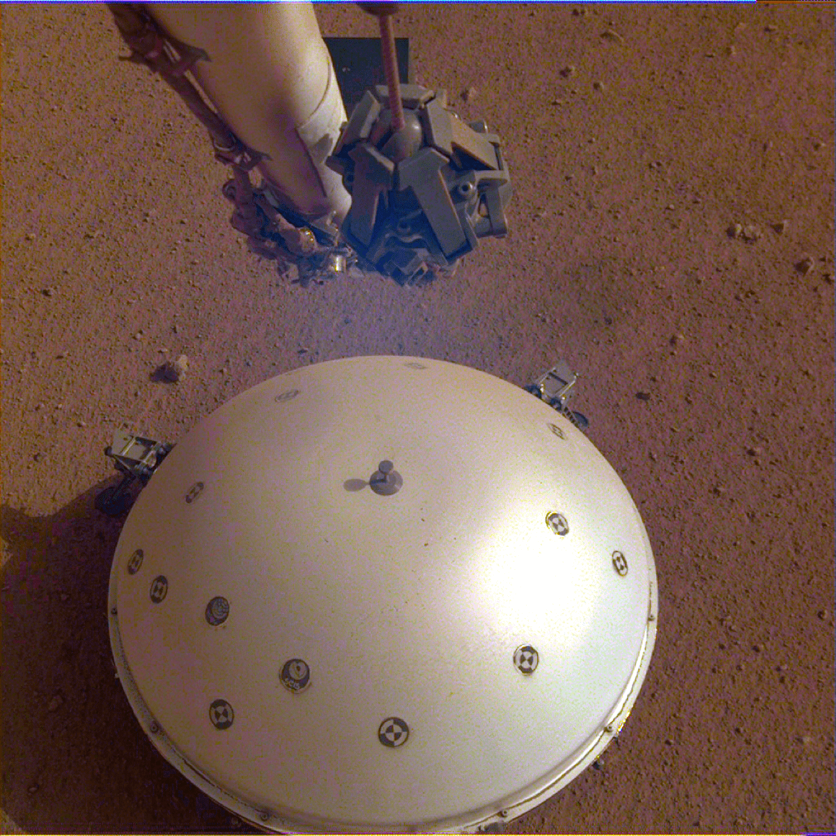 a robotic arm above a white dome structure on a red earth landscape