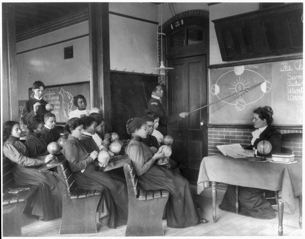 a very old black and white photo of a classroom with over a dozen adult students. most of the students are black, and each of them are holding a miniature globe of the earth. a black man, using a long pointing stick, is gesturing towards the blackboard, where a simple chalk diagram is drawn depicting the different phases and tilts of the earth as it orbits around the sun