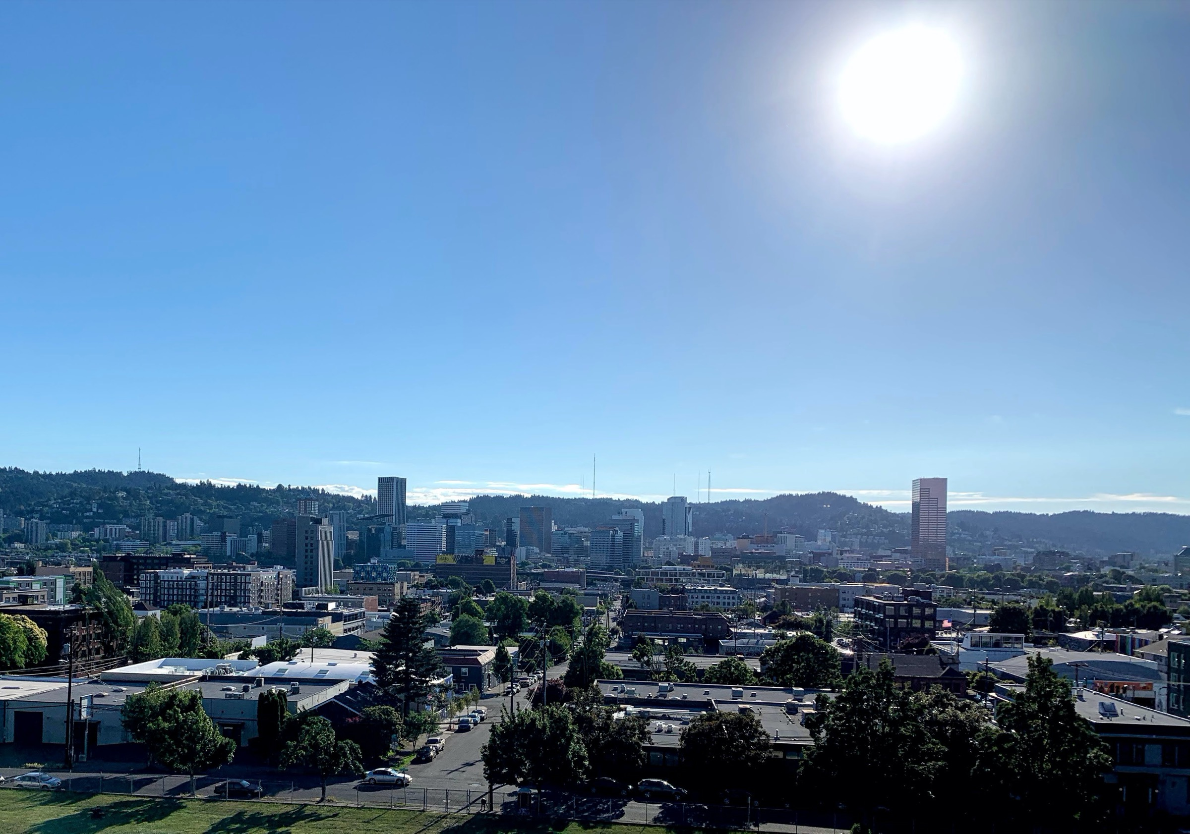 a clear hot day looking at downtown portland with mountains in the distance with the sun in frame
