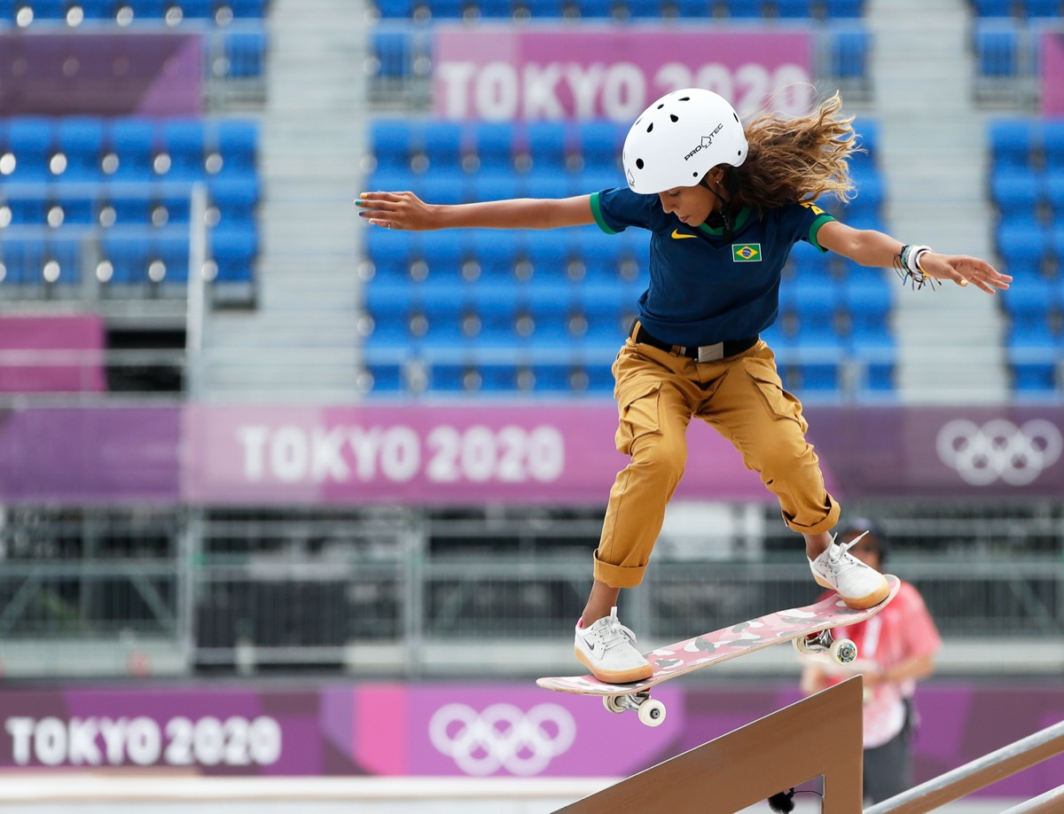 a young brazilian girl in a white helmet, navy polo shirt, and khaki cargos rides a pink and black skateboard over a railing. in the background is an empty auditorium with signs for the tokyo 2020 olympics