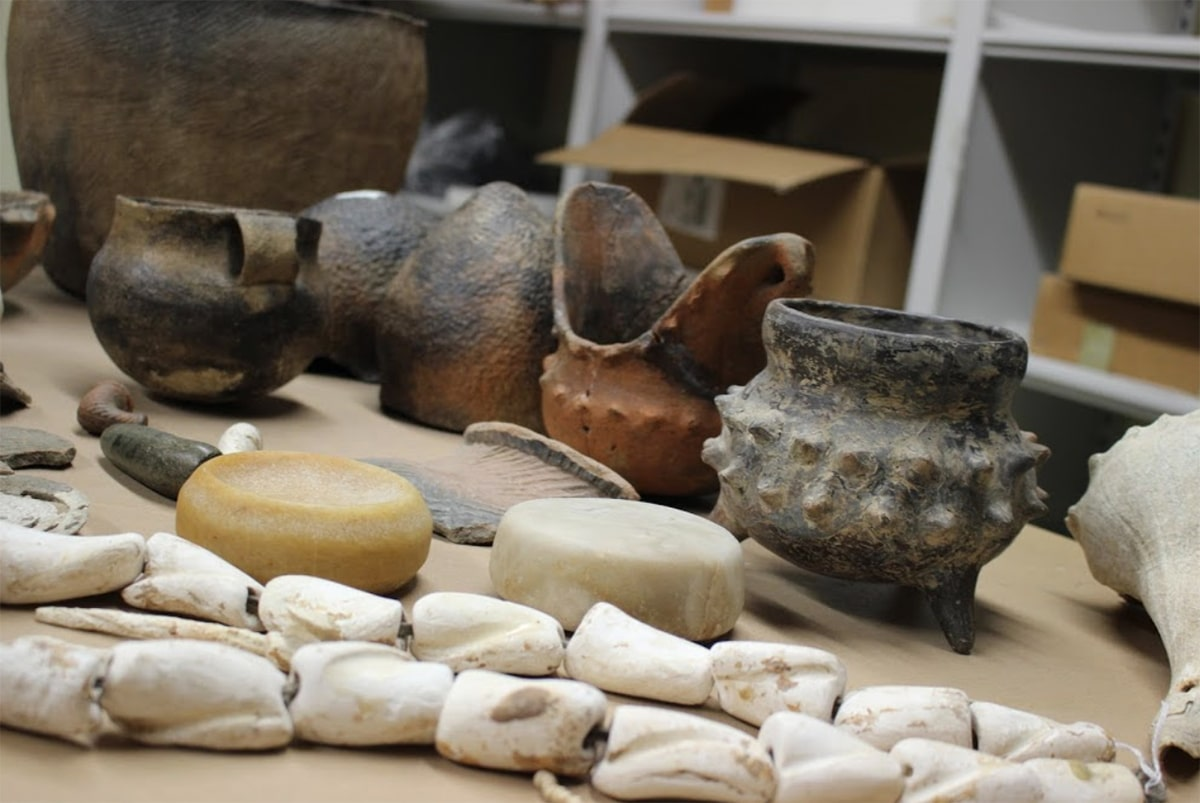 Table with various pieces of pottery including two examples of fire pots.