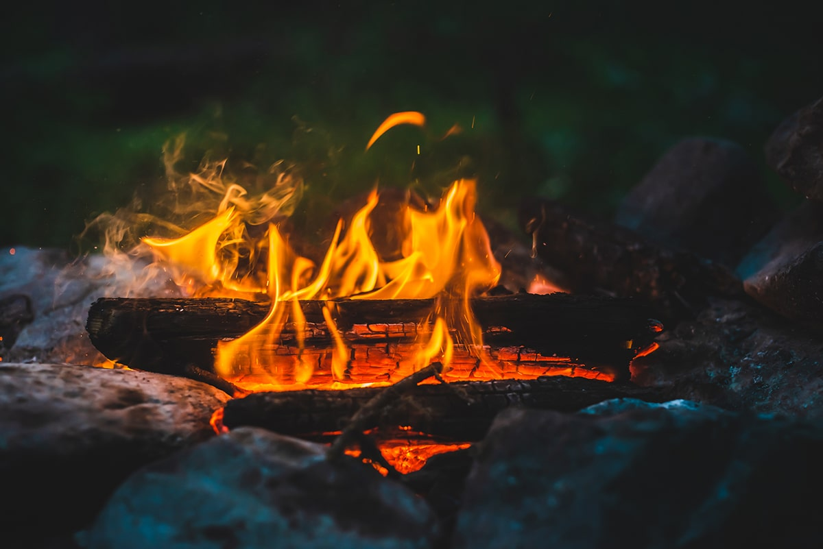 Close up of a campfire with orange flames.