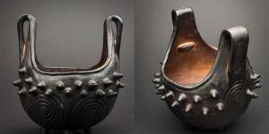 Cherokee firepot with two looped handles. Black on the outside with cone protrusions along the rim.