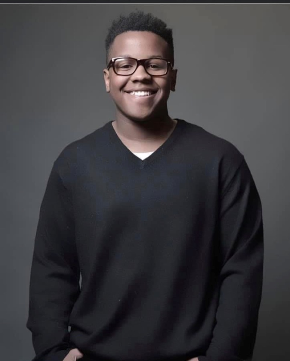 a smiling young black man with glasses and a black sweater