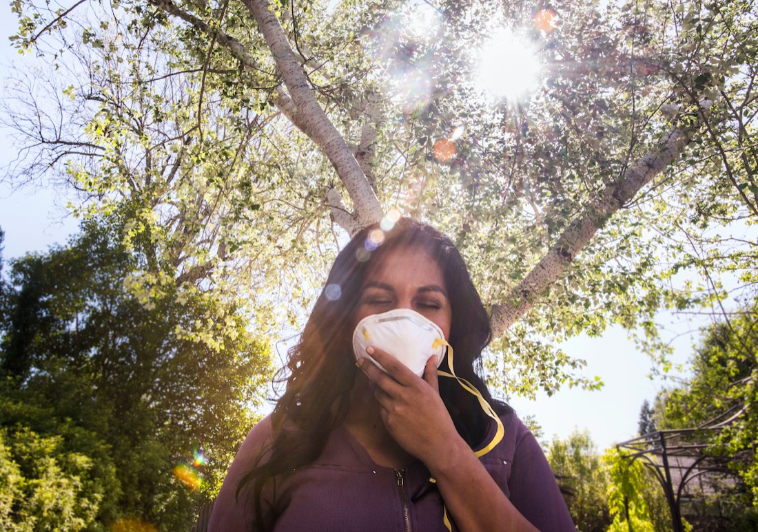 a latina woman holds a mask against her face, sun streams through trees in the background