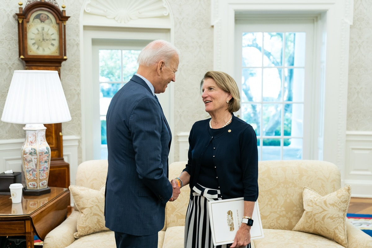 a man and a woman shake hands in an office of the white house