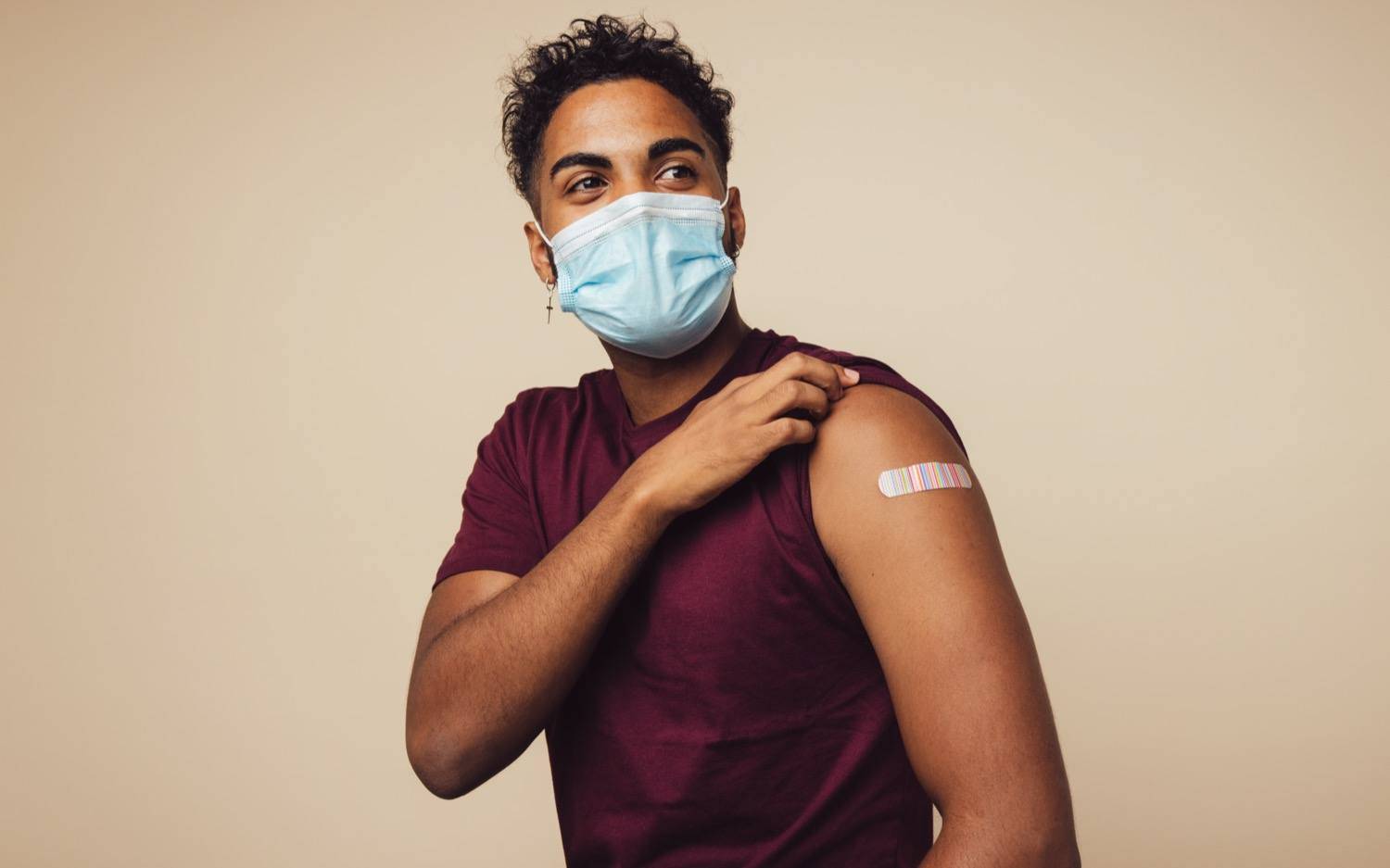 a brown man wearing a mask pulling up his left shift sleeve revealing a bandaid on his arm after a shot