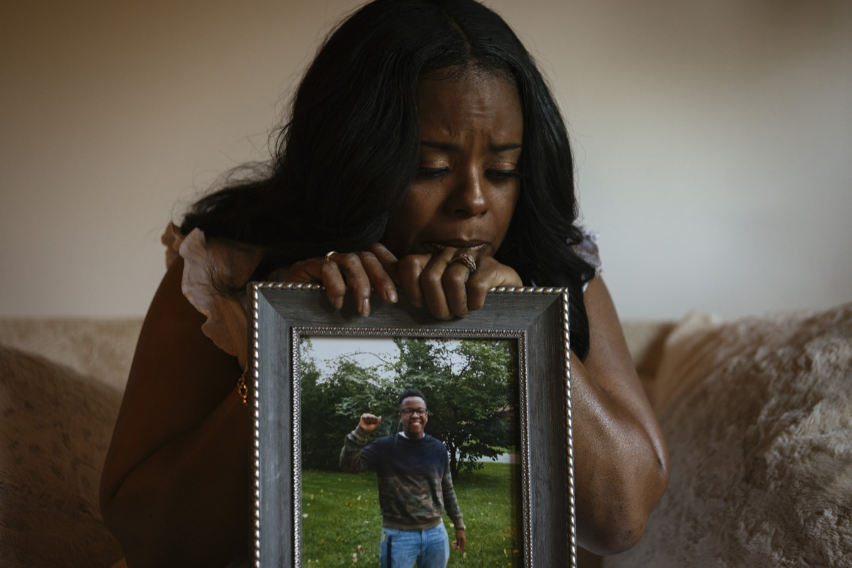 a black woman sadly holding a framed portrait of her son